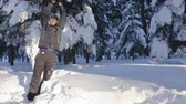 atlama : Young man jumping in the snow and laughing, on a sunny winter day in the forest