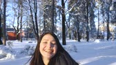 Girl has fun jumping in winter snowy park Archivo de Video