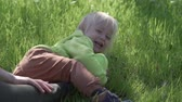 Happy toddler laughs lying on the lawn