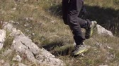 antreman : The man runs and jumps over the stone. Close-up of a legs on a grass and stone Stok Video