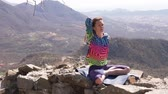 Young athletic woman meditating on the top of a mountain, zen yoga meditation practice in nature Wideo