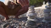 Close-up family, hand folds a pyramid of stones on the seashore.