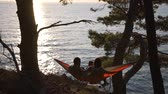 A young family on a hammock meets the sunset.