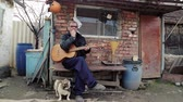 bedelaar : Russian old man in dirty clothes and a guitar drinking vodka, sitting in the yard in the village. Drinking man. National Russian man drinking and playing guitar