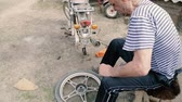 electric scooters : an elderly man repairs his bike in the yard in the village,the old man repairs the wheel of the motorcycle Stock Footage