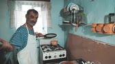блины : Happy smiling older man throwing a pancake in a pan in my old kitchen. Positive emotions, facial expressions, kitchen game