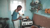bedelaar : Happy smiling older man making a pancake in a pan in my old kitchen. Positive emotions, facial expressions, kitchen game