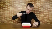 kluski : untidy young guy eating instant noodles