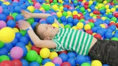 vista aérea : boy lying on multi colored plastic balls in big paddling pool