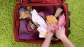 hysterics : Top view - woman hands are packing suitcase for a journey. Girl dreams about travell. Summer clothing and diving mask with snorkel. Stock Footage
