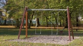 abduction : Abandoned empty swings swaying in the wind at children playground outdoors -  in a park an autumn sunny day.