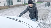 Young Woman Cleaning Car from Snow and Ice. Female removing cleaning snow from Parked Car. Snowing Storm Car Covered Winter Cold Day