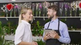 greenhouse : A man in a garden apron shows white flowers in a beautiful woman in glasses. The concept of gardening and country life. Slow motion. Stock Footage