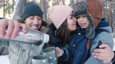 famílias : Family drinking tea in the winter forest. Family concept
