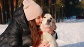 evcil hayvan : Woman hugging a dog in the winter forest Stok Video