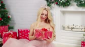 подарки : A blond woman looking at a beautiful christmas present.