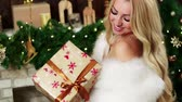 коробка подарка : A blond woman looking at a beautiful christmas present.