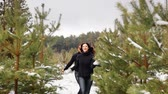ilişkiler : couple having fun in the winter forest. They run through the snow and laugh. The camera is moving. Merry Christmas concept. Stok Video