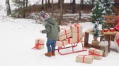 Рождественский подарок : A little boy puts gifts on a sled. Concept happy christmas. Scarf and hat. Red sled. Стоковые видеозаписи