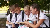 uczeń : Children read a textbook in the schoolyard