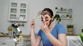 seler : girl put on cosmetic mask eats celery at mirror in kitchen