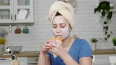 toallas de cocina : girl with mask on face bites and chews hamburger in kitchen