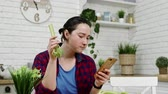 seler : woman with smartphone in hand eats celery at kitchen
