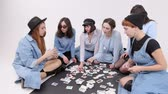 команда : A group of women is sitting on the floor. Women choose the style of clothing in the pictures.