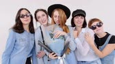 womens : A group of women in denim clothes posing in a white studio. A bunch of flowers in their hands. Women in glasses and hats