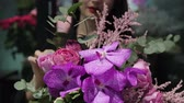 декоратор : Professional woman florist makes the bouquet from pink flowers tulips, roses, orchids and solidago.