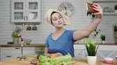 seler : girl with facial mask makes selfie eating celery in kitchen Wideo
