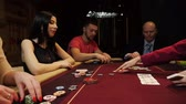 nervoso : People are playing poker. Two men and two woman. Casino gamble.