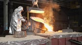 fornalha : Man working with liquid metal in factory. Metal factory sparks