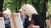 colégio : Poltava, Ukraine - may 2019: A group of women of different ages are learning to draw pictures in the park