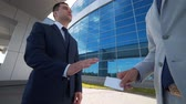 convince : Two business man exchanging business cards and talking Stock Footage