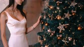 Beautiful girl in a light dress decorates a Christmas tree this year