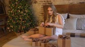 Young beautiful girl wraps a Christmas gift