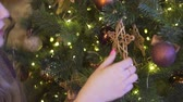 Girl hands decorate christmas tree close up.