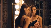 ayartmak : Portrait of a beautiful woman trying on black underwear in front of a mirror. Stok Video
