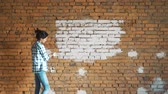 dry wall : A young girl paints a brick wall in her house with a roller. Painting walls with a roller. Paint the bare walls with a roller of white paint. Stock Footage