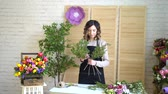 arranjando : Florist at work: pretty young blond woman holds fashion modern bouquet of different flowers with peone and roses in craft paper Vídeos