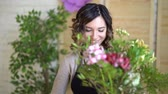 compor : Florist at work: pretty young blond woman holds fashion modern bouquet of different flowers with peone and roses in craft paper Vídeos
