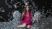 glee : Happy young woman in pink dress celebrates New year or birthday on black background with confetti Stock Footage