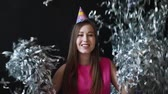 длинношерстный : Happy young woman in pink dress celebrates New year or birthday on black background with confetti Стоковые видеозаписи
