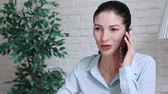 кресло : a woman at a table in the office talking on the phone.