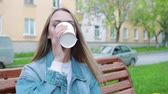 bebida quente : drinks and people concept - happy young woman or teenage girl drinking coffee from paper cup sitting on on city street bench