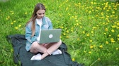 блог : woman sitting in park on the green grass with laptop, notebook. Student studying outdoors