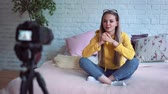 блог : Funny woman blogger recording video. Girl beauty blogger sitting on the bed, writes a video to your blog.