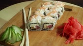 сакэ : Fresh sushi, rolls on the table. Dark background. Sushi sticks.