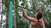 insan vücudu : Young attractive man is doing exercise on the parallel bars outdoors. Guy shirtless is engaged in amateur sports. Active lifestyle concept. Stok Video